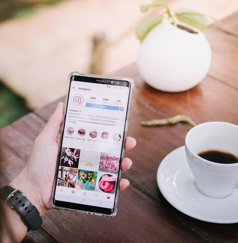 femme tenant un mobile avec appli instagram